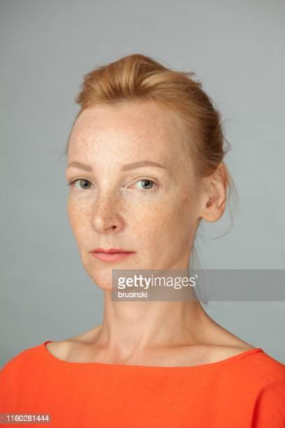studio-porträt der blondine mit sommersprossen auf grauem hintergrund - frauen über 30 stock-fotos und bilder