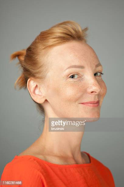 studio portrait of woman blonde with freckles on gray background - three quarter front view stock pictures, royalty-free photos & images