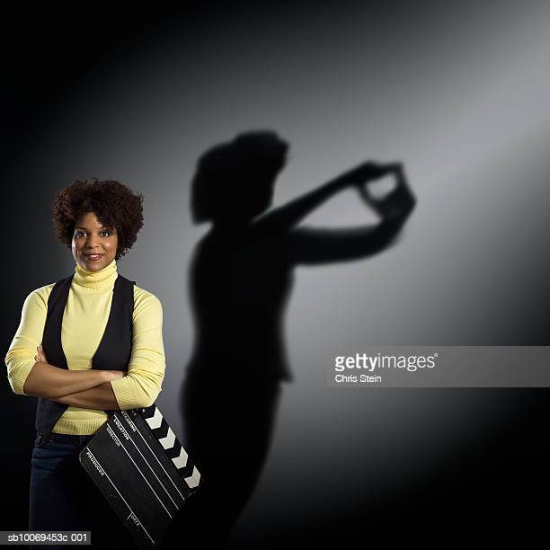 studio portrait of woman holding clapperboard, with shadow behind - grip film crew stock photos and pictures