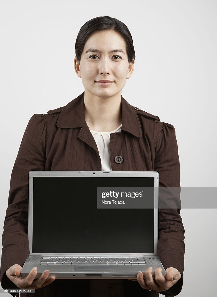 Studio portrait of woman holding laptop : Stockfoto