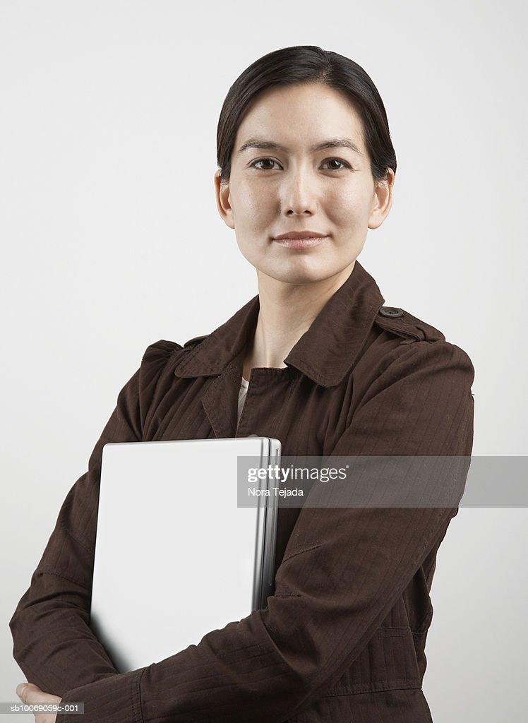 Studio portrait of woman holding laptop : Stockfoto