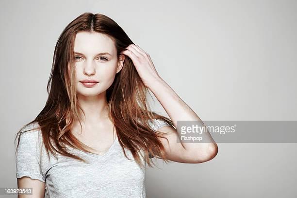 studio portrait of woman - 髪に手をやる ストックフォトと画像