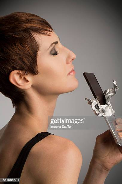 Studio portrait of woman with eyes closed holding up dark chocolate bar