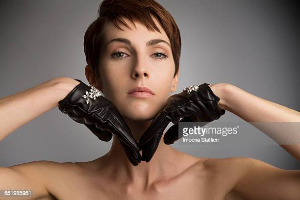 studio portrait of woman with hands on chin wearing black leather gloves - clavicle stock photos and pictures