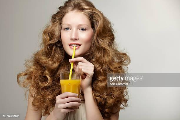 Studio portrait of woman with wavy hair drinking orange juice