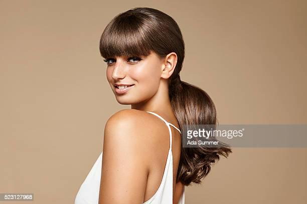 studio portrait of young brunette woman - pferdeschwanz stock-fotos und bilder
