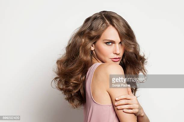 studio portrait of young brunette woman - wavy hair stock pictures, royalty-free photos & images