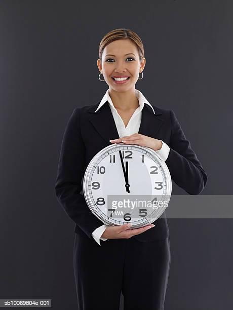 Studio portrait of young businesswoman holding clock