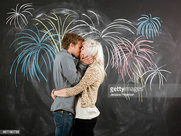 Studio portrait of young couple embracing in front of blackboard