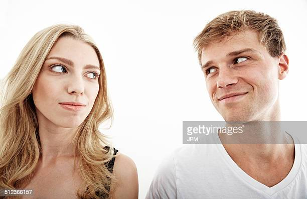 Studio portrait of young couple looking sideways at each other