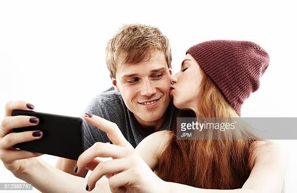 Studio portrait of young couple taking selfie on smartphone