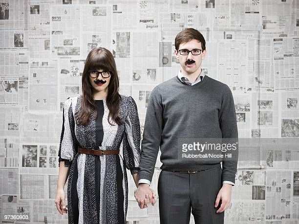 Studio portrait of young couple wearing fake moustaches