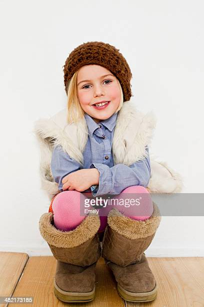 studio portrait of young girl in oversize boots - little girls dressed up wearing pantyhose stock photos and pictures