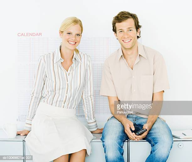 Studio portrait of young man and woman in office