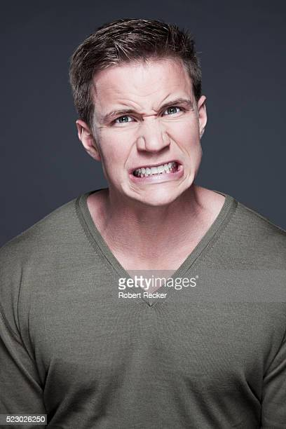 studio portrait of young man clenching teeth - clenching teeth stock pictures, royalty-free photos & images