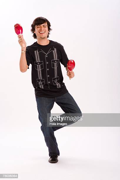 studio portrait of young man dancing with maracas - maraca stock photos and pictures