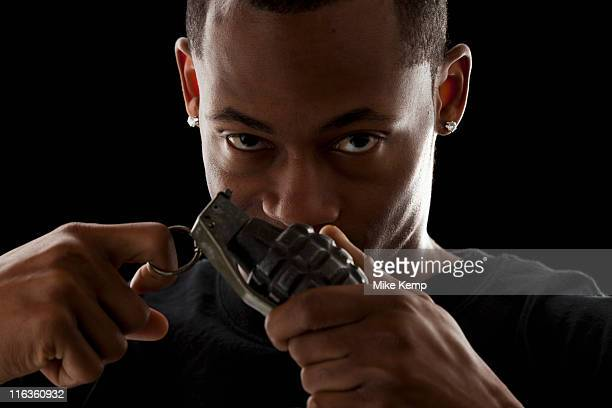 studio portrait of young man holding grenade - hand grenade stock pictures, royalty-free photos & images