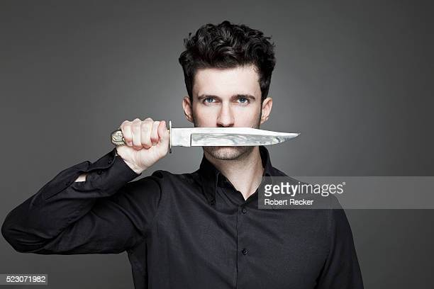 Studio portrait of young man holding knife