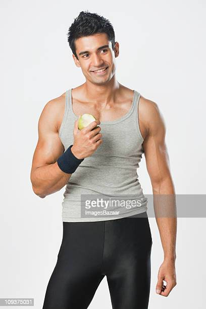 Studio portrait of young man in sports clothing holding apple