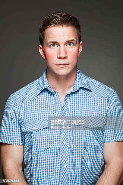 studio portrait of young man - embarrassment stock photos and pictures
