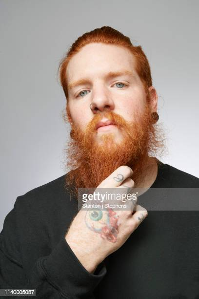 studio portrait of young man with red hair stroking beard - funky stock pictures, royalty-free photos & images