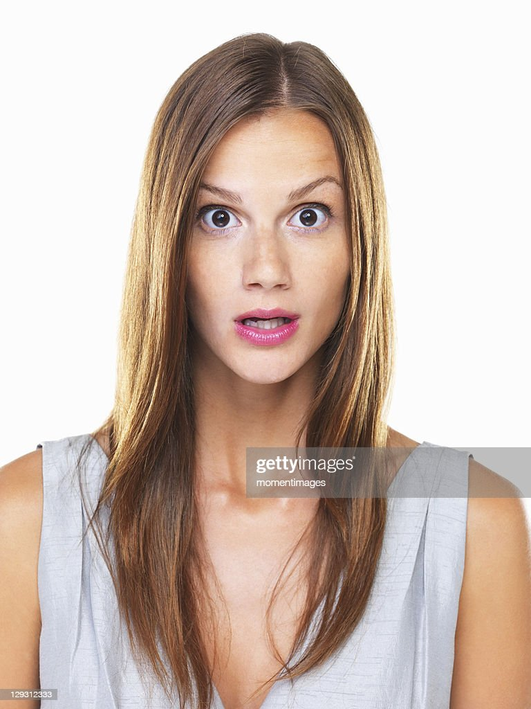 Studio portrait of young surprised woman staring on camera : Stock Photo