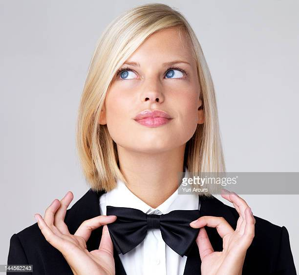studio portrait of young waitress adjusting bow tie - bow tie stock pictures, royalty-free photos & images