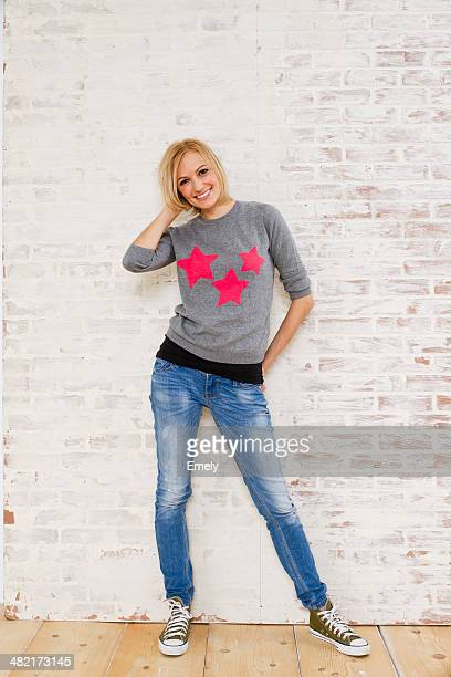 studio portrait of young woman and brick wall - white pants stock pictures, royalty-free photos & images