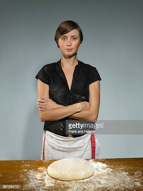 Studio portrait of young woman baking bread dough