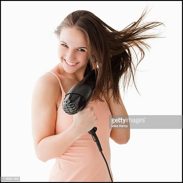 Studio portrait of young woman blow drying hair