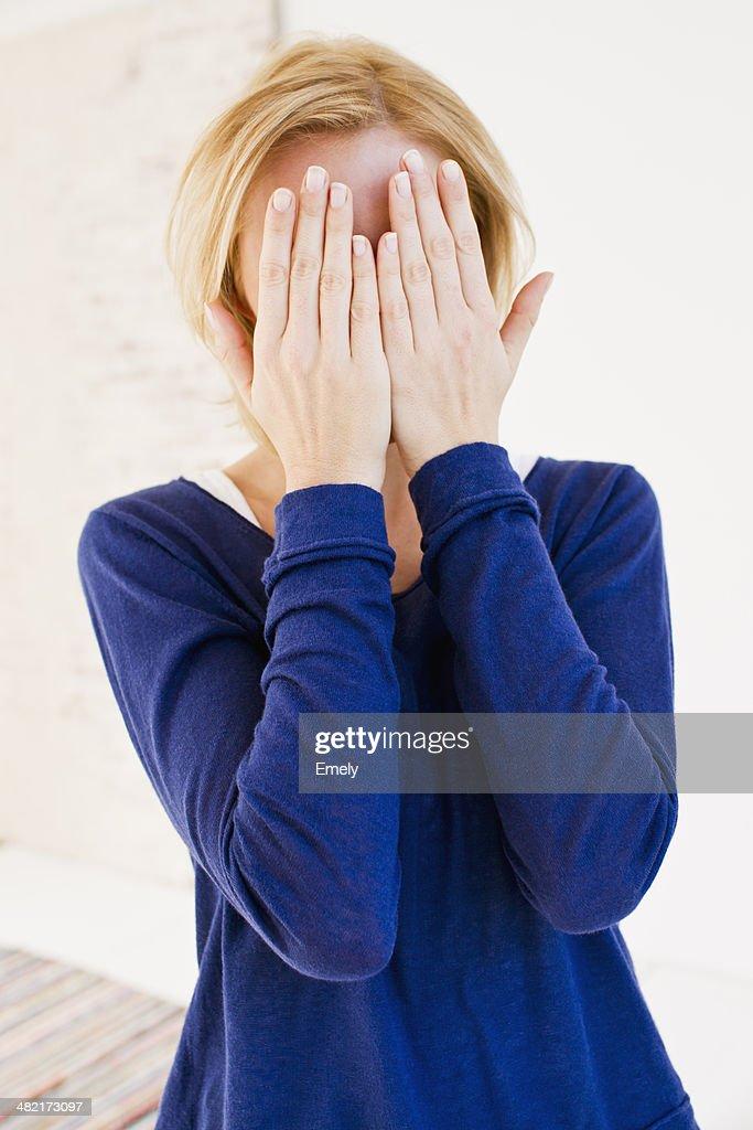 Studio portrait of young woman hiding behind hands : Stock Photo