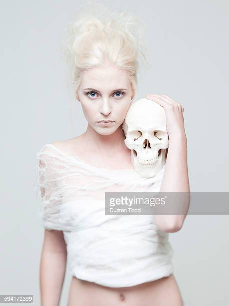 Studio portrait of young woman holding skull