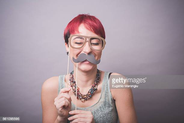 studio portrait of young woman holding up mustache and spectacles in front of face - capelli colorati foto e immagini stock