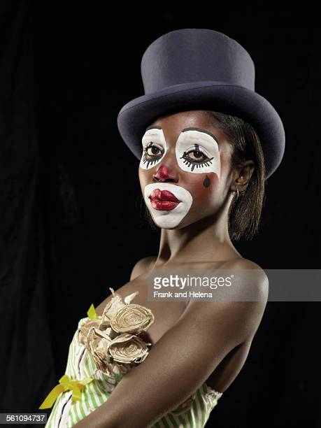Studio portrait of young woman in clown face paint wearing top hat