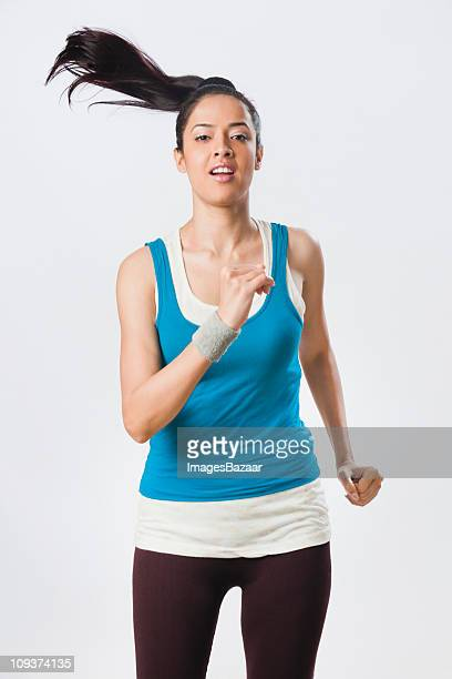 studio portrait of young woman jogging - 黒髪 ストックフォトと画像
