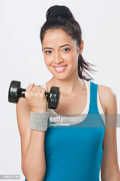 Studio portrait of young woman lifting hand weights