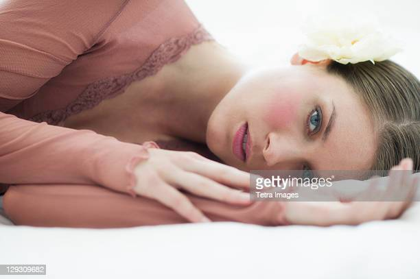 Studio portrait of young woman lying on bed