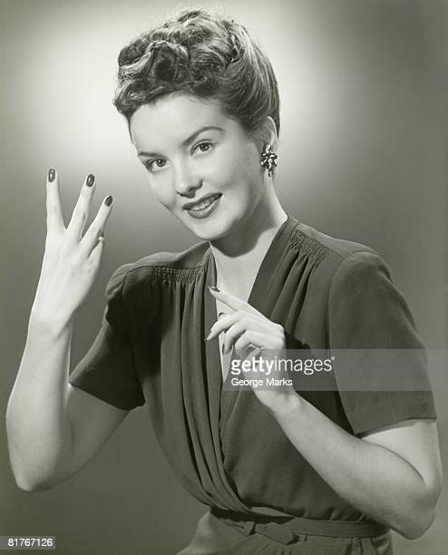 Studio portrait of young woman making hand gesture