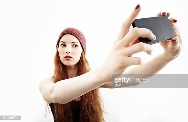 Studio portrait of young woman making selfie on smartphone