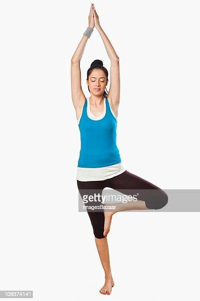 studio portrait of young woman practicing yoga - tree position stock photos and pictures