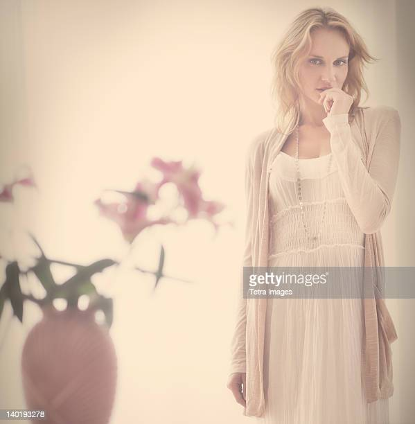 Studio portrait of young woman standing behind vase