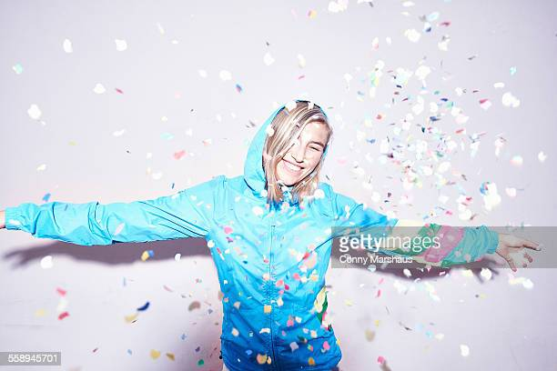 Studio portrait of young woman throwing confetti