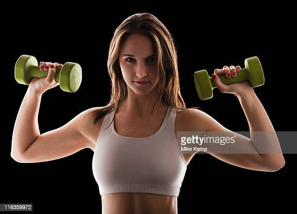 Studio portrait of young woman using hand weights