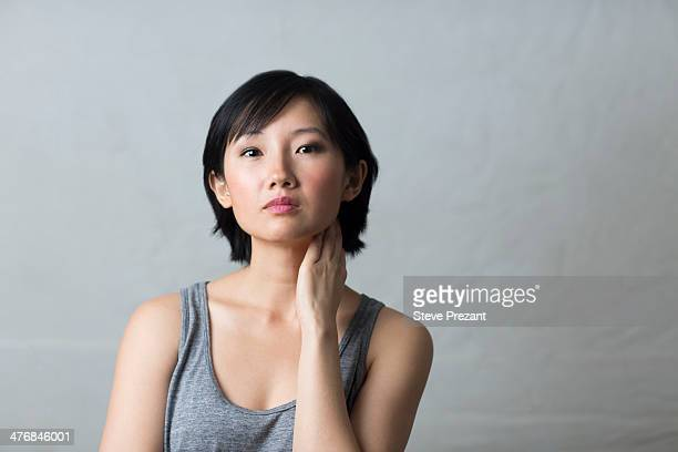 studio portrait of young woman with hand on neck - curiosity stock pictures, royalty-free photos & images