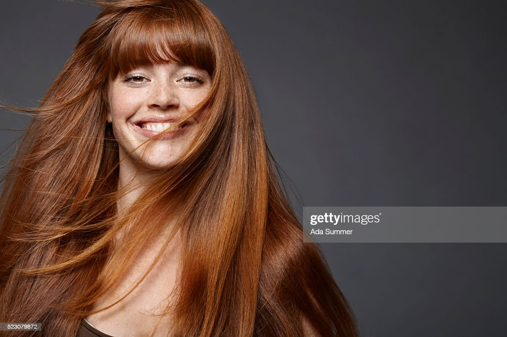 Studio portrait of young woman with long brown hair : Stock Photo