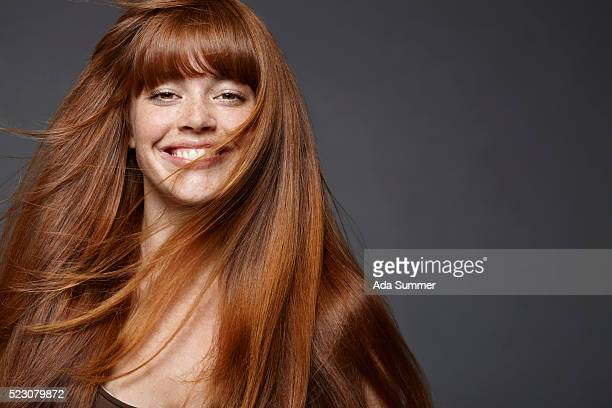 studio portrait of young woman with long brown hair - steil haar stockfoto's en -beelden