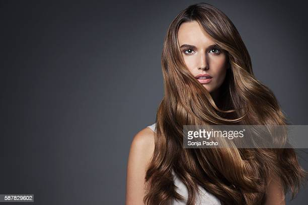 studio portrait of young woman with long brown hair - brown hair photos et images de collection