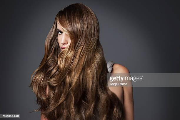 studio portrait of young woman with long brown hair - long hair stock pictures, royalty-free photos & images