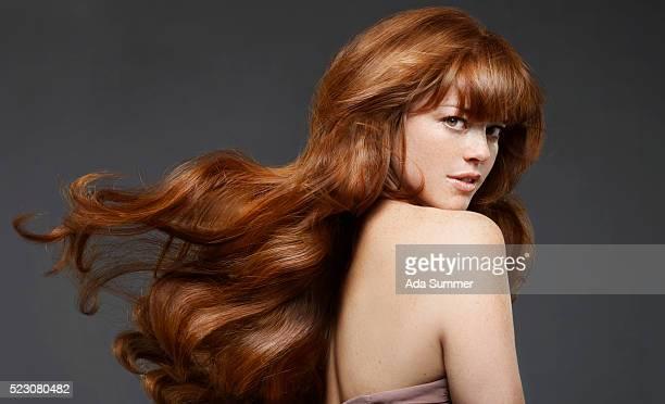 studio portrait of young woman with long hair - welliges haar stock-fotos und bilder