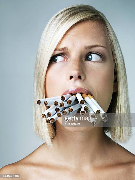Studio portrait of young woman with mouthful of cigarettes